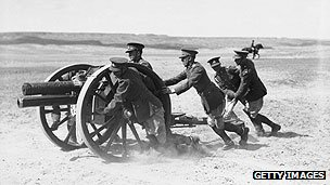 Soldiers pushing a gun over sand