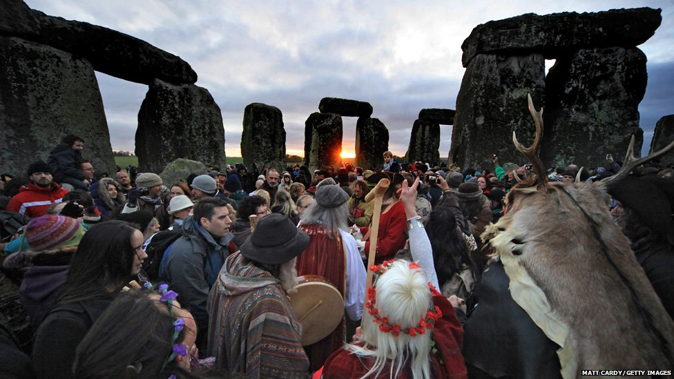 Druids, pagans and revellers cheer as the sun rises at Stonehenge in Wiltshire, England