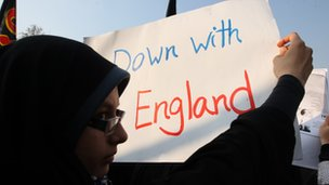"A protester holds a poster displaying the message ""Down with England"" in Tehran"