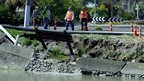 Government officials survey a collapsed bank and broken water line on the banks of the Avon River in Christchurch