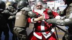 A man in a Father Christmas costume is arrested by police