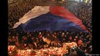 People stand under a giant Czech flag as they arrive to light candles at the base of a statue of St. Wenceslas to mourn the death of former Czech President Vaclav Havel