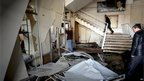 Syrian security men inspect damage inside the General Intelligence headquarters, which was targeted by a suicide attack, in Damascus (23 December 2011)