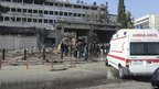 People gather around the entrance of a damaged building after a car bomb blew up at security sites in Damascus (23 December 2011)