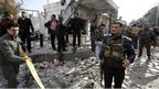 Members of Syrian security are seen at the site of a suicide bombing in Damascus, Syria (23 December 2011)