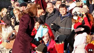 The Duchess of Cambridge talks to a little girl as she attends St Mary Magdalene Church