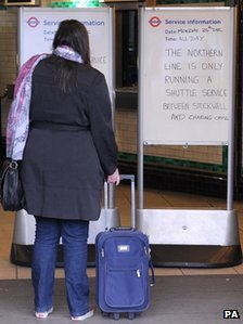 A woman reads a sign at Clapham North Tube station on Monday