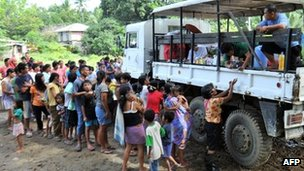 Local residents queue for food and medical supplies outside an evacuation centre in Cagayan de Oro City on 23 December 2011