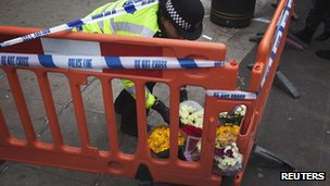 A police officer lays flowers outside the Foot Locker shop on Oxford Street in central London