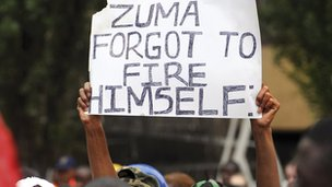 A protestor holding an anti-Zuma poster