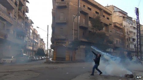 A protester throws back a tear-gas canister fired by security forces in the Syrian city of Homs (27 December 2011)