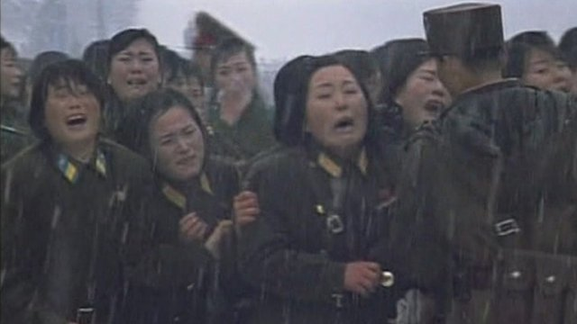 Women in military dress crying at the funeral