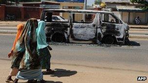 Young girls walk past a vehicle burnt on 4 November on a street of Damaturu, Yobe State, Nigeria.
