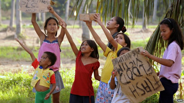 Children hold up placards on a street in Cagayan de Oro