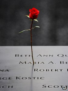 A rose rests on a list names inscribed on 9/11 Memorial