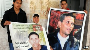 Relatives of Mohamed Bouazizi holding up portraits of him in Tunisia, November 2011