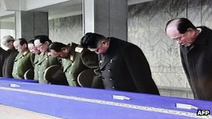 Screen grab from North Korea state television shows Kim Jong-un (in black overcoat) bowing at the memorial service in Pyongyang on 29 December 2011