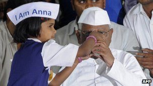 Indian social activist Anna Hazare breaks his fast with a glass of juice offered by a child at the Mumbai Metropolitan Region Development Authority (MMRDA) recreation ground in Mumbai on December 28, 2011