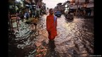 A Buddhist monk walks on a flooded street in central Bangkok, October 2011