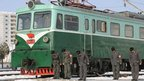 North Korean railway workers bow next to trams during a service for the late North Korean leader Kim Jong-il in this photo taken by Kyodo, 29 December 2011