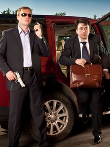 Man with gun and man with briefcase