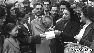 Woman using coupon in Petticoat Lane on first day of clothes rationing