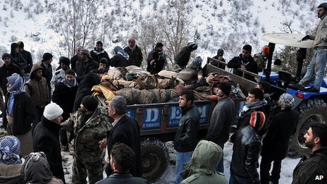 Victims' bodies on tractor trailor after air raid, 29 Dec 11
