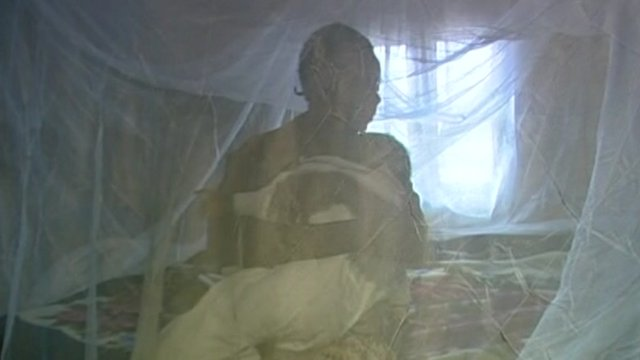 A woman sits under a malaria net with her baby
