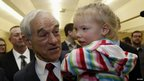 Texas Representative Ron Paul holds a child at an event in Le Mars, Iowa 30 December 2011