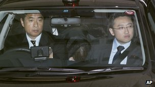 Makoto Hirata, a member of Aum Shinrikyo, rear centre, sits in a police car