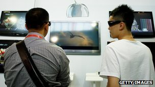 People looks at 3D televisions during the 14th China Beijing International High-tech Expo (CHITEC) at the China International Exhibition Centre in Beijing, 18 May 2011