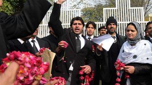 Pakistani lawyers hold rose petals as they voice support for Mumtaz Qadri