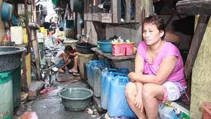Clarita, sitting outside her one-room home in Manila