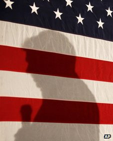 Rick Perry's shadow is cast on a flag in Boone, Iowa, on 31 December 2011