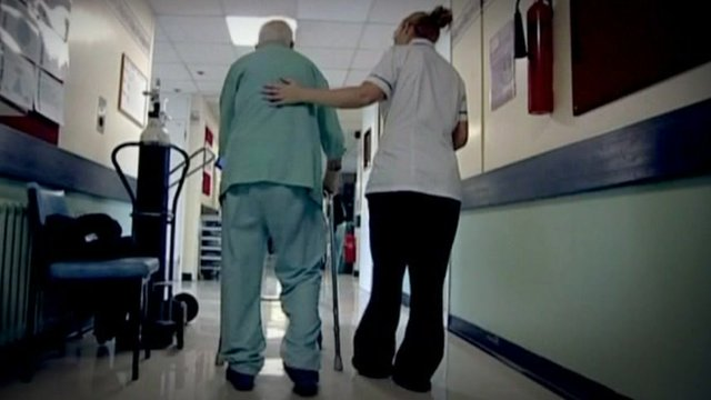 Elderly man being assisted by nurse