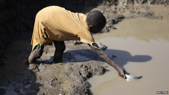 Sudanese girl collects water from muddy water