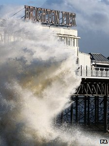 Waves crash on the seafront near Brighton Pier in Brighton, East Sussex