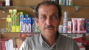 Shopkeeper Esidene Sawesi standing at his new counter, with boxes of toothpaste and cigarettes stacked behind him