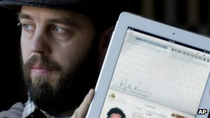 Martin Reisch holds up his iPad displaying his scanned passport