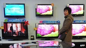 A woman walking past television sets on display at an electronics and home appliances store in Zhengzhou in central China&#039;s Henan Province (file photo)