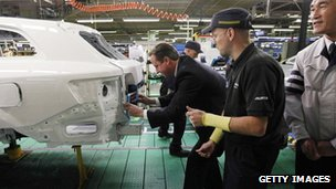 Prime Minister David Cameron installs a badge on a car at a Toyota plant on November 24, 2011, in Burnaston, United Kingdom