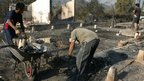 Workers cleans the debris of a house destroyed by a massive forest fire affecting the commune of Quillon in Bio Bio region, some 500km south of Santiago, on 2 January 2012.