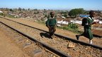 School children walk along a railway line in Kibera, a slum in Nairobi (Kelsey Smith)