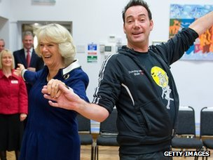 The Duchess of Cornwall, president of the National Osteoporosis Society, and Craig Revel Horwood dance during a visit to a school in 2009.