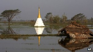 A small temple is seen submerged in a flooded rice field near a house destroyed by la devastating cyclone in 2008.