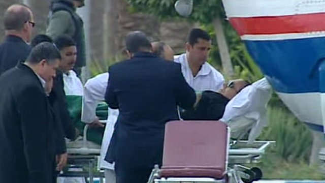 Hosni Mubarak is stretchered onto a plane.