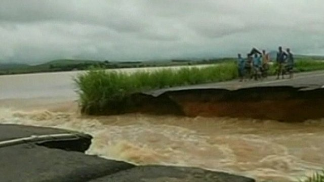 People standing on edge of road destroyed by the force of the flood