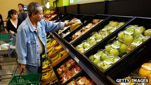 A shopper selecting fruit