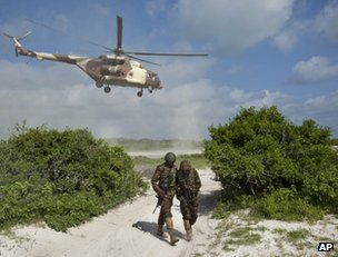Kenyan soldiers shield themselves from the downdraft of a Kenyan helicopter at  Bur Garbo, inside Somalia (image from 14 December)