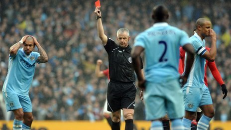 Chris Foy shows Vincent Kompany a red card
